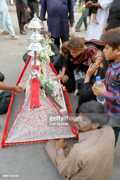 Pakistani Shia Muslims sitting near symbolic baby cots of the babies belongs to the family of Hazrat Imam Hussain who sacrificed their lives in Karbala war for Allah and Islam during a Muharram procession on main road