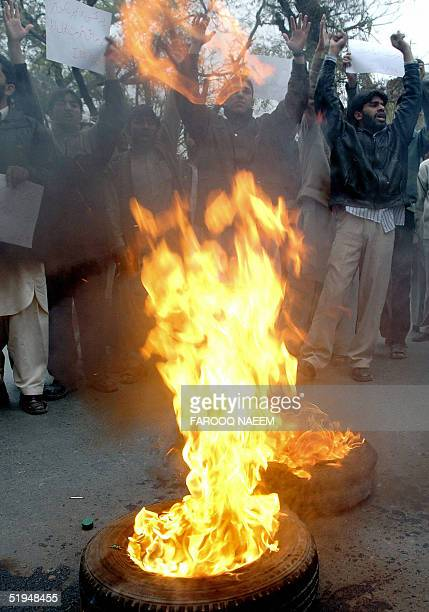 Pakistani Shiite activists chant antigovernment slogans as they stand behind a barrage of burning tyres during a demonstration in Islamabad 13...