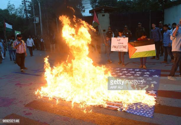 TOPSHOT Pakistani Shiite demonstrators gather as they burn a US flag during a protest outside the US consulate in Lahore on May 16 2018 Israel has...