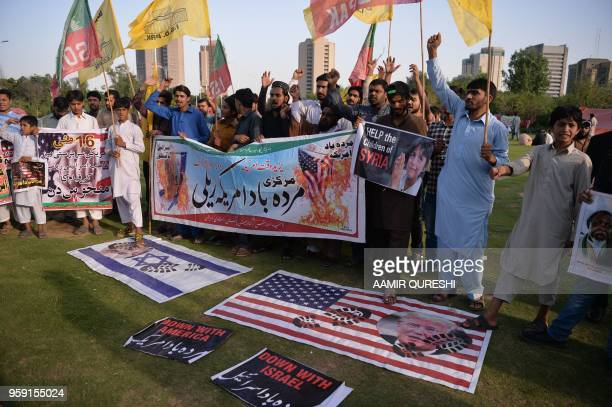 Pakistani Shiite demonstrators stand on the US and Israeli bearing with images of US President Donald Trump and Israeli Prime Minister Benjamin...