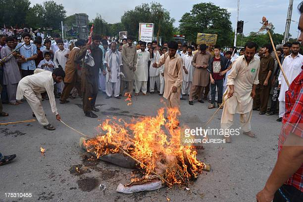 Pakistani Shiite Muslim demonstrators beat a burning effigy representing Israel during a rally against Israel and the United States to mark the...
