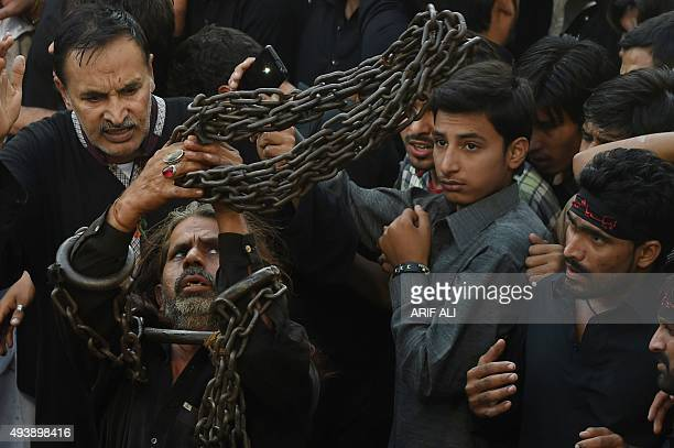 A Pakistani Shiite Muslim devotee uses chains to selfflagellate during an Ashura procession to commemorate the martyrdom of Imam Hussain the grandson...