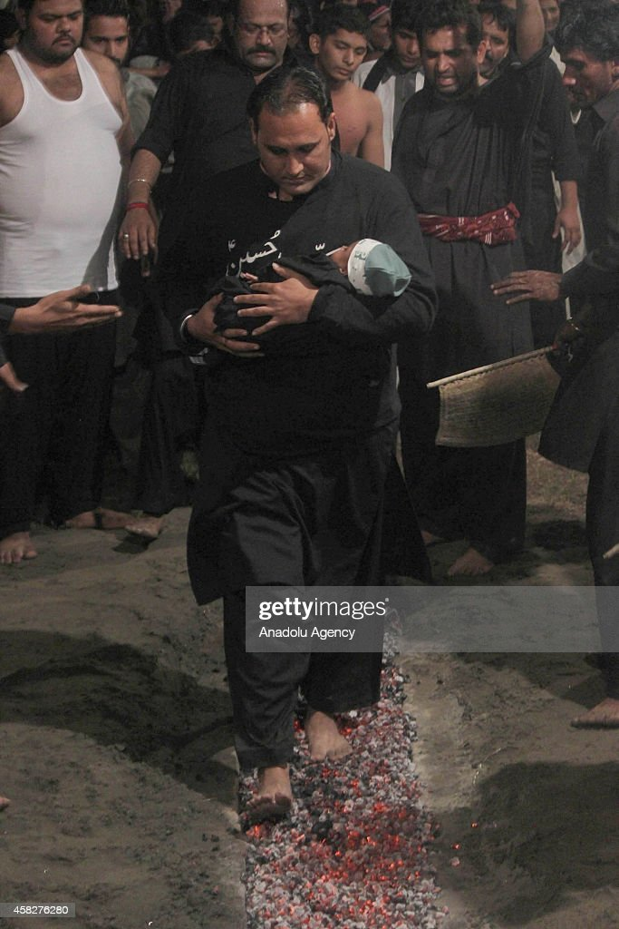 Pakistani Shiite Muslim Holds A Baby While Walking On