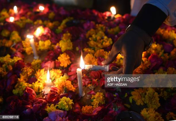 Pakistani Shiite Muslim lights a candle during a vigil in Karachi on February 14 to pay tribute to the victims of a suicide bombing in Lahore...