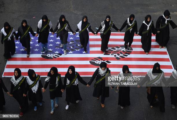 Pakistani Shiite Muslim march over a US flag during a rally against Israel and the United States to mark the AlQuds during the holy month of Ramadan...