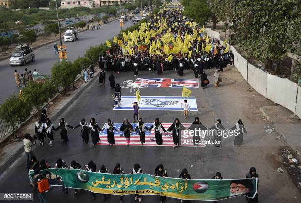 Pakistani Shiite Muslim march over the flags of Israel United States and Britain during a rally to mark the AlQuds on the last Friday of the holy...