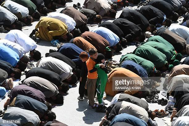 Pakistani Shiite Muslim pray in a Ashura procession in Quetta on October 12 2016 Ashura is a period of mourning in remembrance of the seventhcentury...