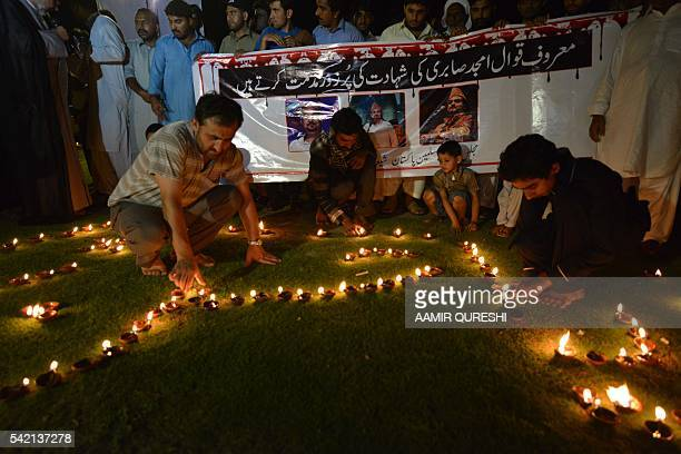 Pakistani Shiite Muslim protesters light oil lamps to pay tribute to Sufi musician Amjad Sabri who was killed in an attack by unknown gunmen in...