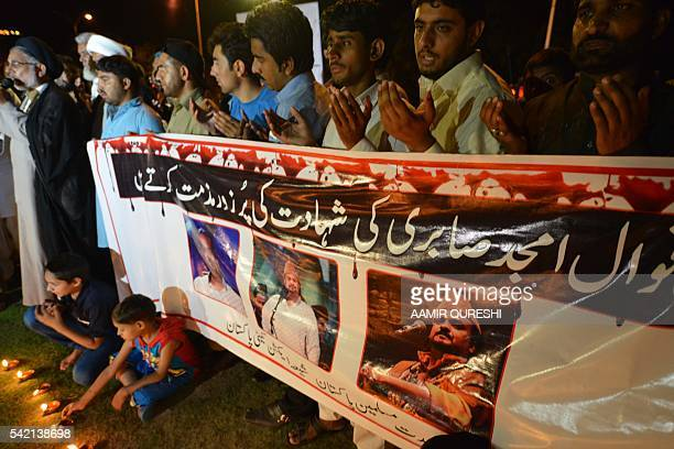 Pakistani Shiite Muslim protesters pray as they pay tribute to Sufi musician Amjad Sabri who was killed in an attack by unknown gunmen in Islamabad...