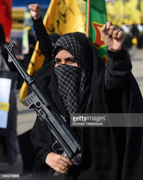 A Pakistani Shiite Muslim woman shouts slogans while holding a toy gun during a rally against Israel and the United States to mark AlQuds day on the...