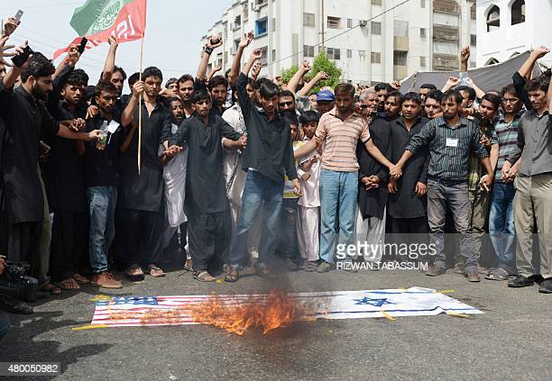 Pakistani Shiite Muslims burn US and Israeli flags during a procession to observe the death anniversary of Imam Ali the soninlaw of Prophet Mohammad...