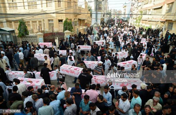 Pakistani Shiite Muslims carry 72 mock coffins during a mourning procession in Karachi on September 12 2019 Shiite Muslims over the world observe...