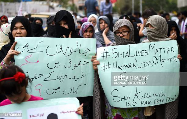 Pakistani Shiite Muslims hold placards as they protest against the suicide blast targeting the Shia Hazara ethnic minority in Karachi on April 14...