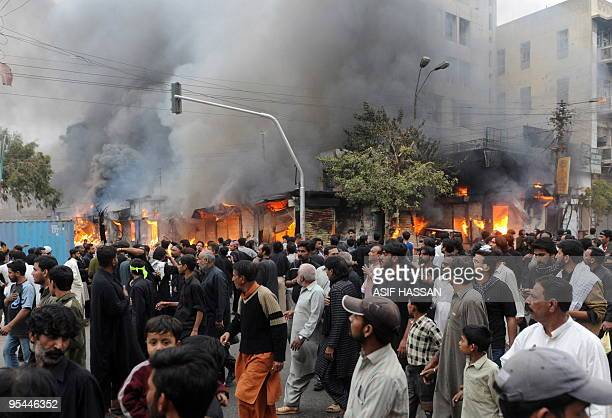Pakistani Shiite Muslims walk past a burning market after the bomb blast during the Shiite Muslim procession on Ashura in Karachi on December 28 2009...