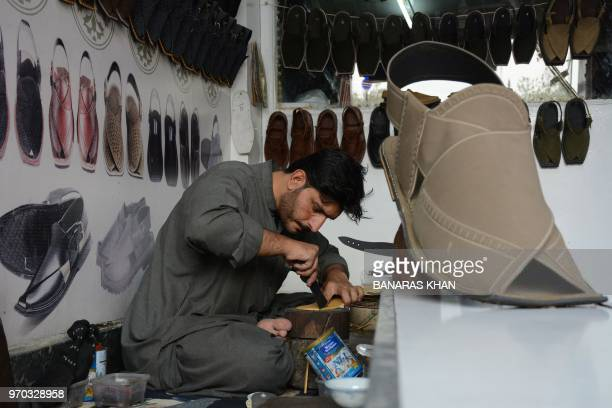 A Pakistani shoe maker makes a new shoe for his customers for the upcoming Muslim festival Eid ul Fitr in Quetta on June 9 2018 EidulFitr which marks...