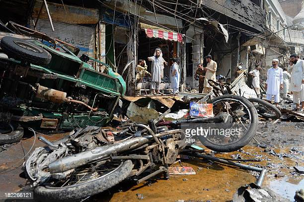 Pakistani shop onwers gather at the site of a bomb explosion in the busy Kissa Khwani market in Peshawar on September 29 2013 A bomb explosion killed...