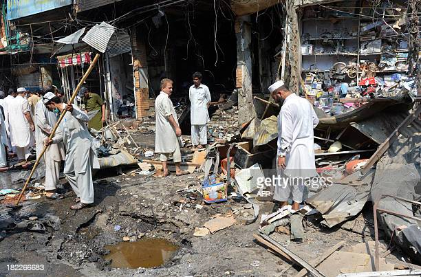Pakistani shop owners gather at the site of a bomb explosion in the busy Kissa Khwani market in Peshawar on September 29 2013 A car bomb killed at...