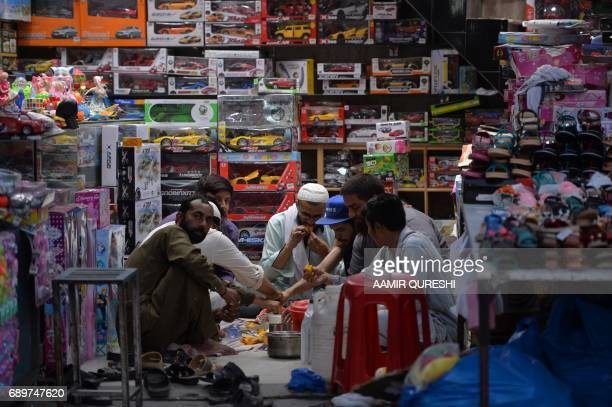 Pakistani shopkeepers break their fast at a market in Rawalpindi on May 29 2017 Muslims throughout the world are marking the month of Ramadan the...