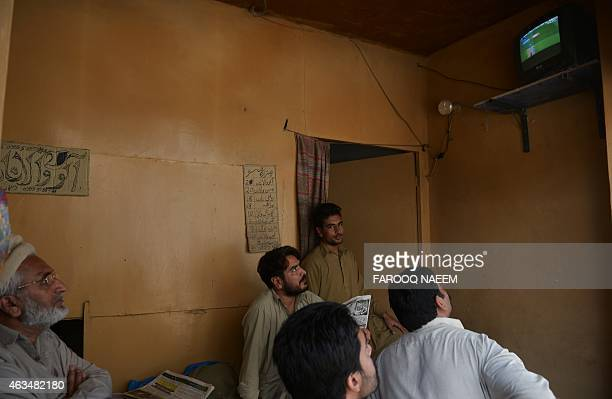 Pakistani shopkeepers watch the live broadcast of the Cricket World Cup match between Pakistan and Indian at a market in Rawalpindi on February 15,...