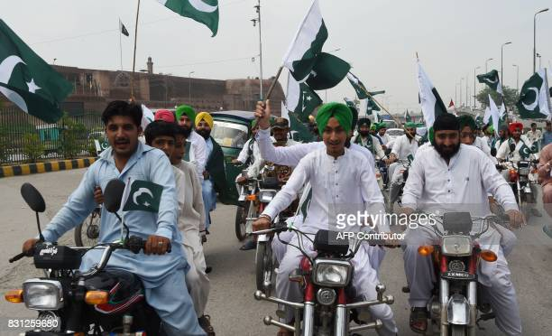 Pakistani Sikhs hold nationals flags as they march during the celebration to mark the country's Independence Day in Peshawar on August 14 2017 This...
