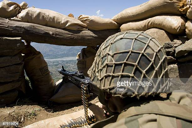 Pakistani soldier aims his weapon on top of a mountain overlooking the Swat valley at Banai Baba Ziarat area on May 22 2009 in northwest Pakistan...