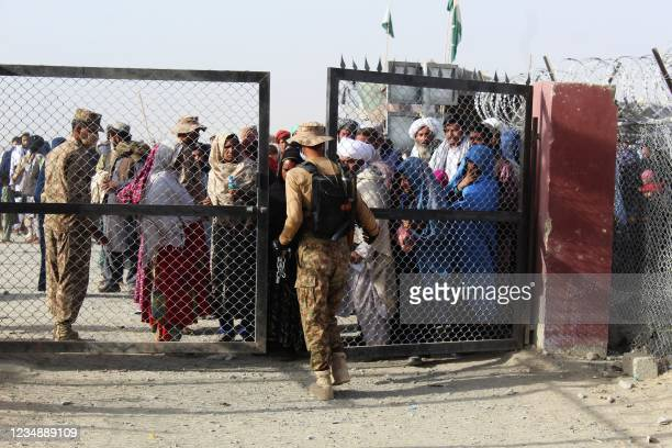 Pakistani soldier holds a gate as Afghan and Pakistani people wait to enter Afghanistan through the Pakistan-Afghanistan border crossing point in...