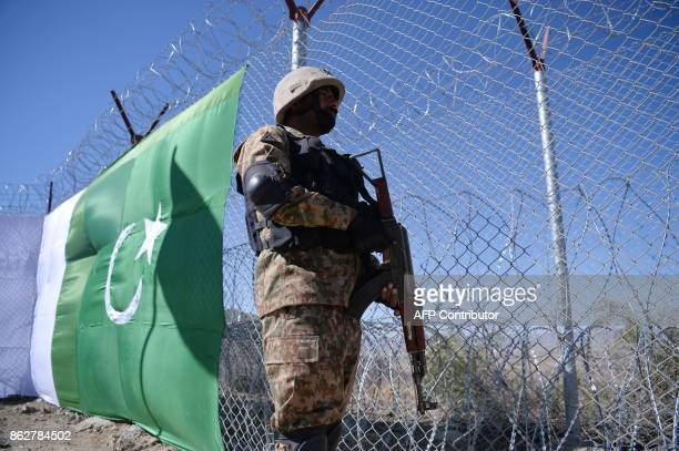 A Pakistani soldier keeps vigil next to a newly fenced border fencing along with Afghan's Paktika province border in Angoor Adda in Pakistan's South...