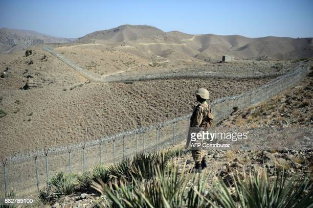 A Pakistani soldier keeps vigil next to a newly fenced border fencing along Afghan border at Kitton Orchard Post in Pakistan's North Waziristan...