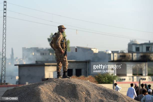 A Pakistani soldier keeps watch as area residents gather at the scene where a Pakistani Army Aviation Corps aircraft crashed in Rawalpindi on July 30...
