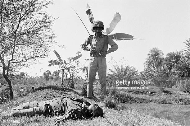 A Pakistani soldier observes a corpse of a soldier following fighting during the war for Bangladeshi independence