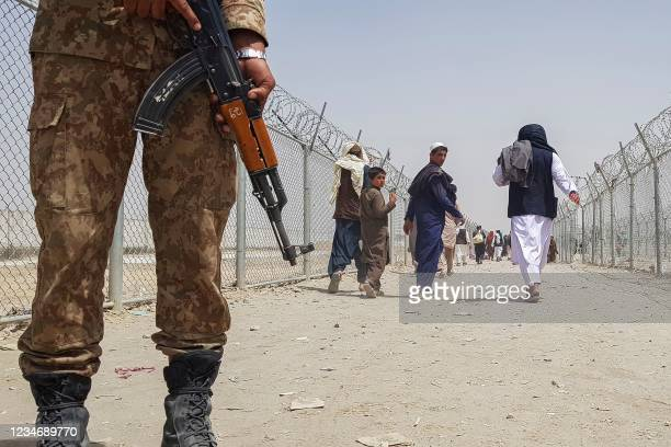 Pakistani soldier stands guard as stranded Afghan nationals return to Afghanistan at the Pakistan-Afghanistan border crossing point in Chaman on...