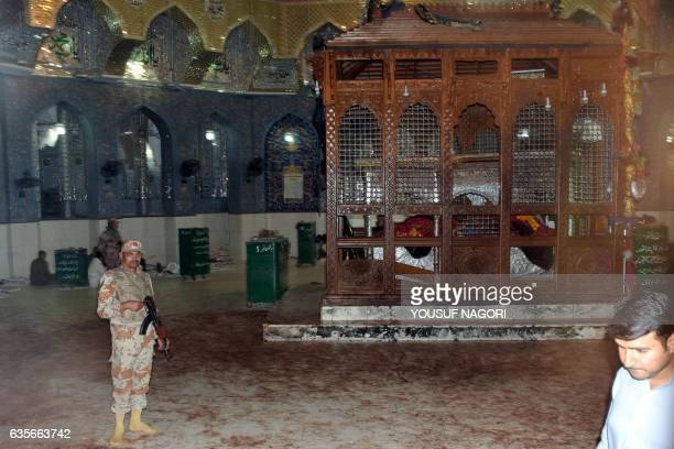 A Pakistani soldier stands guard on a bloodstained floor of the shrine of 13th century Muslim Sufi Saint Lal Shahbaz Qalandar after a bomb explosion...
