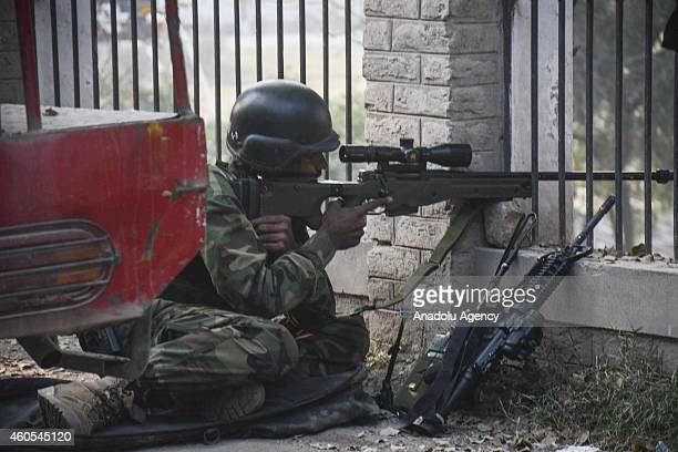 Pakistani soldier takes position near the site of an attack by Taliban gunmen on a school in the northwestern city of Peshawar Pakistan on December...