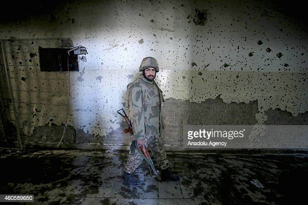 Pakistani soldier walks in the debris of the armyrun school that was attacked by Taliban on Tuesday in northwestern city of Peshawar Pakistan on...