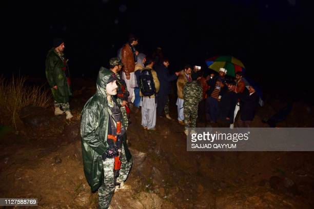 Pakistani soldiers and media personnel gather at the site where the Indian Air Force strike launched on a JaisheMohammad camp at Balakot on February...