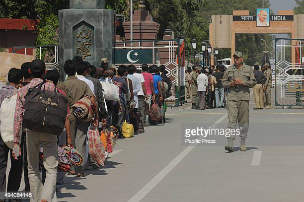 Pakistani soldiers and policemen stand guard as Indian prisoners fishermen who were released from a Pakistani jail as they cross the Wagah Border in...