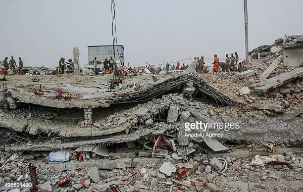 Pakistani soldiers and rescuers search for victims in the rubble of a collapsed factory on the outskirts of Lahore Pakistan on November 5 2015...