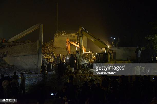 Pakistani soldiers and rescuers search the victims in the rubble of a collapsed factory on the outskirts of Lahore on November 4 2015 At least 16...