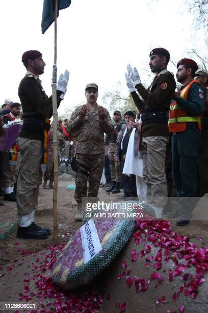 Pakistani soldiers and residents offer prayers next to the grave of Pakistani soldier Khurram Ali who was killed in a gunfight between Indian and...