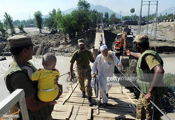 Pakistani soldiers assist flood affected families as they cross over a damaged bridge in the Chakdarra area of Swat on August 4 2010 The...