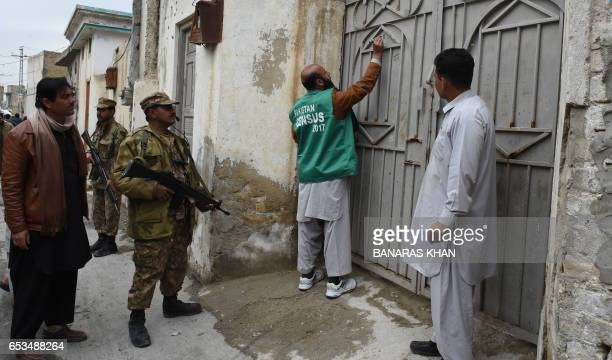 Pakistani soldiers cordon off a street as an official from the Pakistan Bureau of Statistics mark a house after collecting information from a...