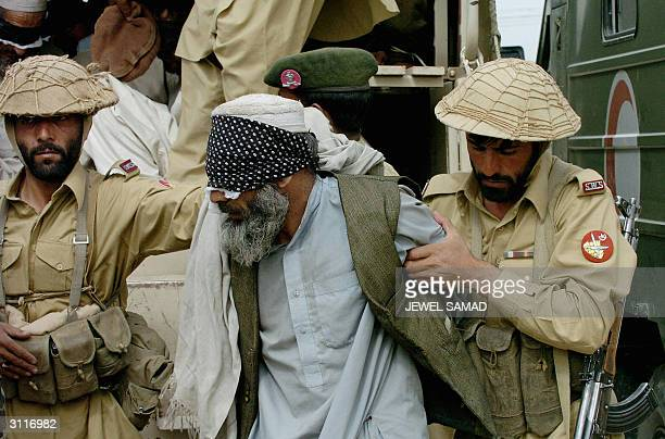 Pakistani soldiers escort a blindfolded detainee at a military base in Wana, South Waziristan district, some 300 kms southwest of Islamabad, 20 March...