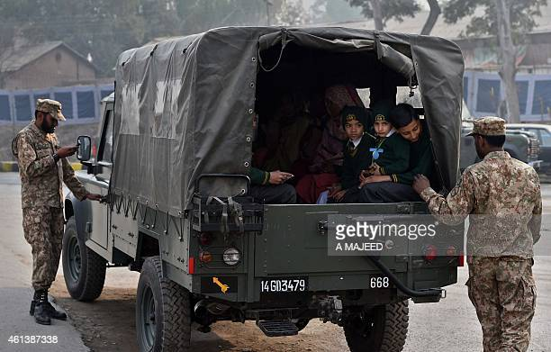 Pakistani soldiers escort students as they leave the Army Public School after it was reopened following an attack there by Taliban militants in...