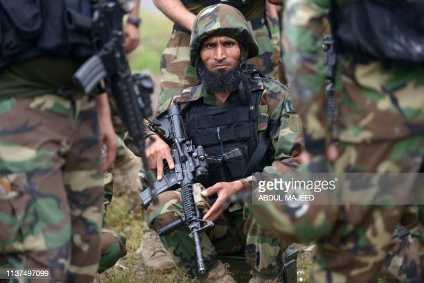 Pakistani soldiers gather beside a demolished hideout of suspected militants during an operation in Peshawar on April 16 2019a police officer An...
