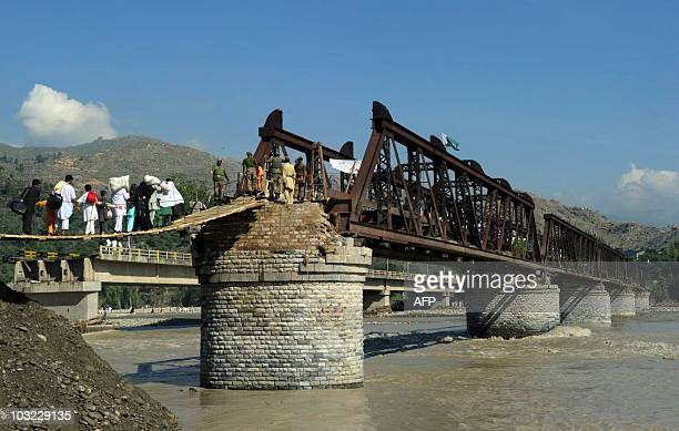 Pakistani soldiers help flood affected families as they cross over a damaged bridge in the Chakdarra area of Swat on August 4 2010 The international...