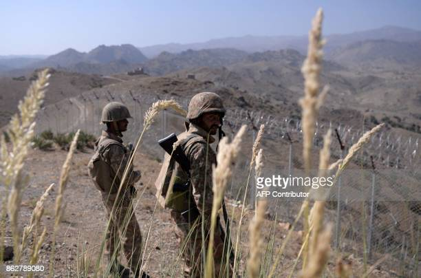 Pakistani soldiers keep vigil next to a newly fenced border fencing along Afghan border at Kitton Orchard Post in Pakistan's North Waziristan tribal...