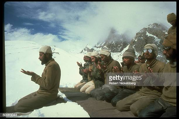 Pakistani soldiers kneeling on rugs in snow praying during 5yrold Indian/Pakistani dispute over icy Karakoram Mts N Kashmir