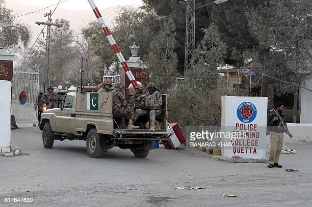 Pakistani soldiers pass through the entrance to The Police Training College in Quetta on October 25 after an overnight militant attack on the...