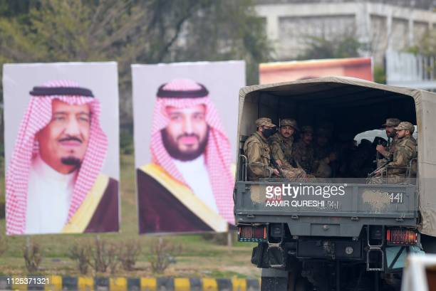 Pakistani soldiers patrol on a street next to welcoming posters of Saudi Arabian Crown Prince Mohammed bin Salman in Islamabad on February 17, 2019....