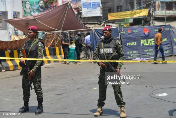 Pakistani soldiers stand alert at the site of a bomb blast outside a Sufi shrine in Lahore Pakistan on May 8 2019 At least eight people including...